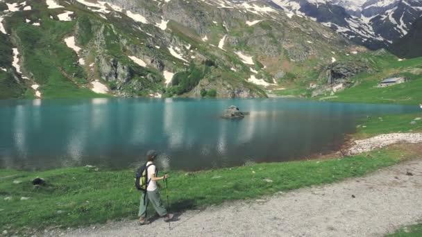 Žena turistiky na modré jezero na Alpy v létě, zasněžené horské pásmo, tónovaný obrázek