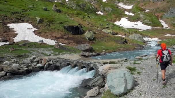 Couple backpackers hiking on footpath crossing mountain stream. Summer adventures and explorationon the Alps.
