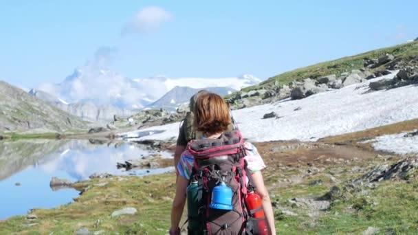 Batohem na chodník v idylické horské krajině s modré jezero, vrchol vysoké hory a ledovce. Letní dobrodružství na Alpy. Zpomalený pohyb