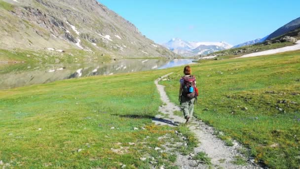 Backpacker hiking on footpath in idyllic mountain landscape with blue lake, high mountain peak and glacier. Summer adventures on the Alps.