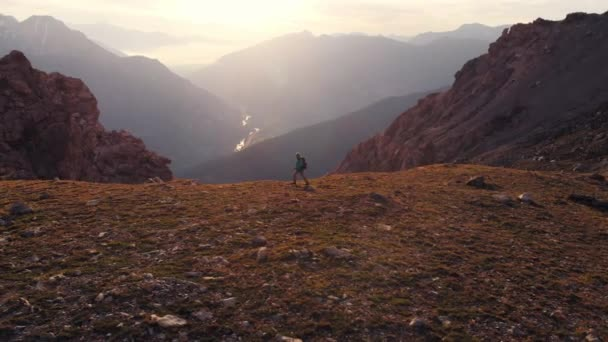 Aerial: Backpacker alpinist hiking to the mountain top, rocky mountain peak in backlight, scenic landscape. Summer adventures on the Alps. Conquering success leader concept