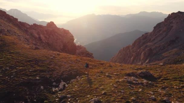 Anténa: Backpacker skialpinistických na vrchol hory horní, skalnaté hory v podsvícení, malebné krajiny. Letní dobrodružství na Alpy. Dobývání koncepce leader úspěch.