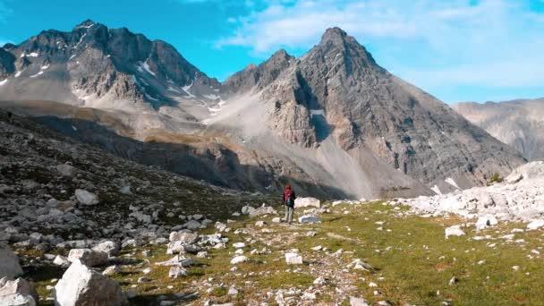 Backpacker žena turistiky na chodník v malebné krajině s vysokou horou, Dolomity, Itálie. Letní dobrodružství na Alpy. Zpomalený pohyb, filmový vzhled
