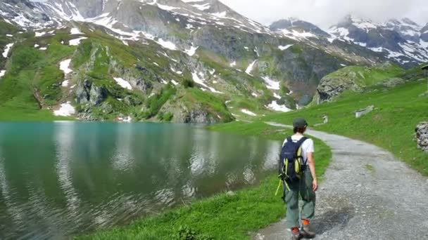 Woman hiking at blue lake on the Alps in summer, snowcapped mountain range, wanderlust concept