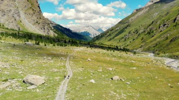 Anténa: pár backpackers v alpském údolí, malebné krajiny. Letní dobrodružství na Alpy. Zpomalený pohyb