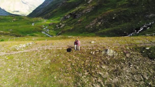 Anténa: pár turistů na blatech v alpském údolí, shora dolů zobrazení. Wanderlust Letní dobrodružství na Alpy. Film vypadat, barevné korekce
