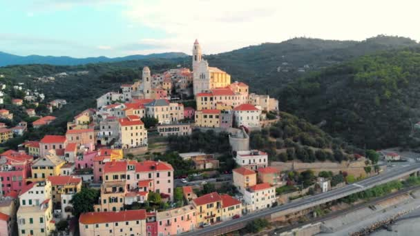 Aerial: flying around Cervo medieval town on the mediterranean coast, Liguria riviera, Italy, with the beautiful baroque church and tower bells. Summer tourism in Italy.