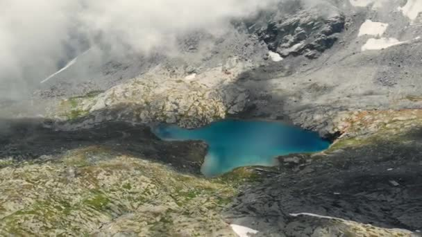 Aerial: flying over high altitude landscape, rocky mountain peaks and blue alpine lake, old military fortification on top. Alps, Andes, Himalaya concept.