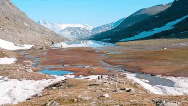Batohem na chodník v idylické horské krajině s modré jezero, vrchol vysoké hory a ledovce. Letní dobrodružství na Alpy.