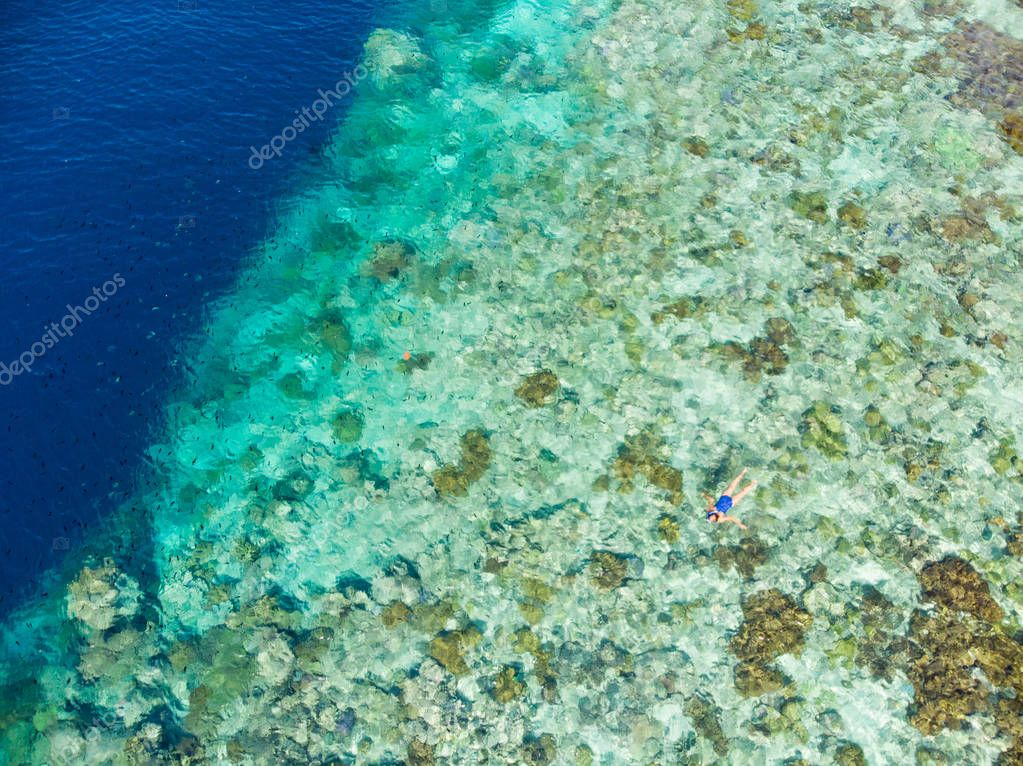 Aerial top down view coral reef tropical caribbean sea, turquoise blue water. Indonesia Moluccas archipelago, Banda Islands, Pulau Hatta. Top travel tourist destination, best diving snorkeling.
