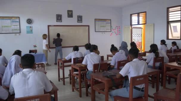 Wab, Indonézia-október 2018: a külföldi európai tanár Holding matematikai osztályban indonéz iskolában a távoli falu wab, Kei szigetek, Moluccas