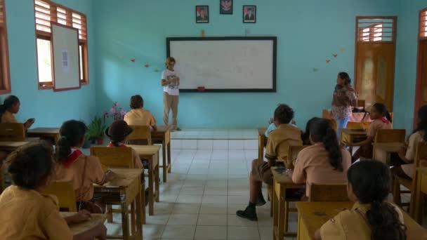 Ngurbloat, Indonézia-október 2018: külföldi európai tanár Holding matematikai osztályban indonéz iskola távoli falu Ngurbloat, Kei szigetek, Moluccas