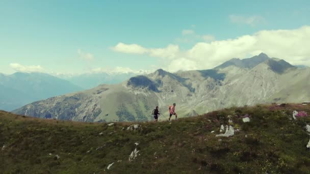 Aerial slow motion: couple backpackers hiking on mountain top, scenic landscape. Summer adventures on the Alps. Conquering success mature adult having fun wellbeing fitness