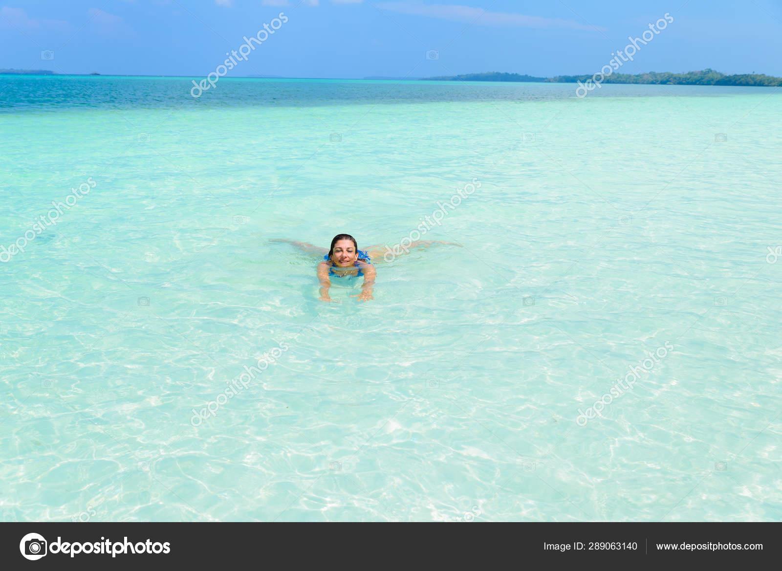 Mujer nadando en mar caribeño turquesa agua transparente