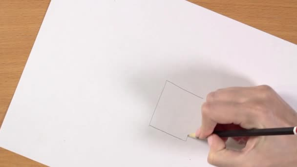 Female hand draws a house with a pencil