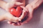 Erwachsene und Kinder Hände holiding rotes Herz, Gesundheitsfürsorge, Liebe, Spende, Versicherung und Familienkonzept