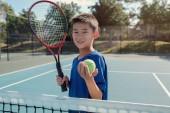 Malé doplnění asijské boy tenista na venkovní modrý kurt