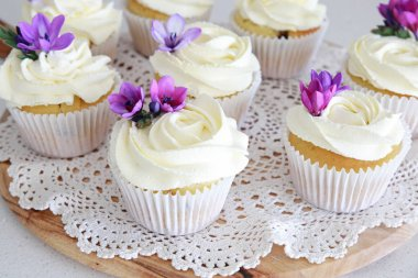 Frosting vanilla cupcakes with purple edible flowers