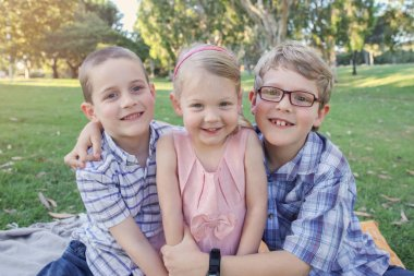 Happy brothers and sister playing at the park