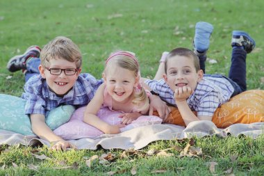 Happy brothers and sister portrait at park, toning