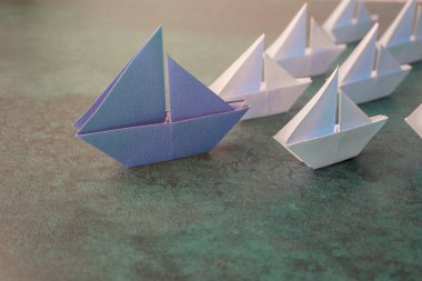 Origami paper ships, leadership business concept.
