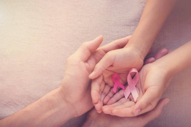 Adult and child hands holding pink ribbons, Breast cancer awareness, abdominal cancer awareness, October pink concept