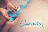 Adult and child hands holding Light blue ribbon, Prostate Cancer Awareness month