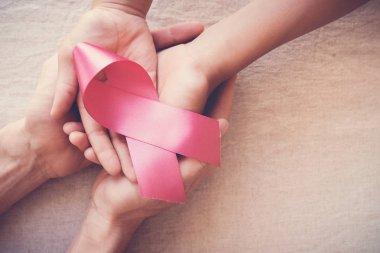 hands holding pink ribbon, breast cancer awareness, October pink concept