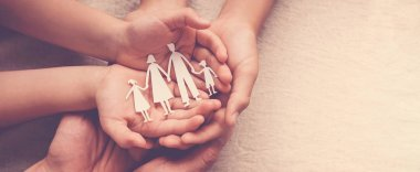 Adult and children hands holding paper family cutout, family hom