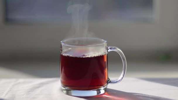 Čaj černý čaj nalévání do šálku transparentní čaj sklo. Čas na čaj. Průhledná Skleněná konvice a šálek. Zpomalený pohyb