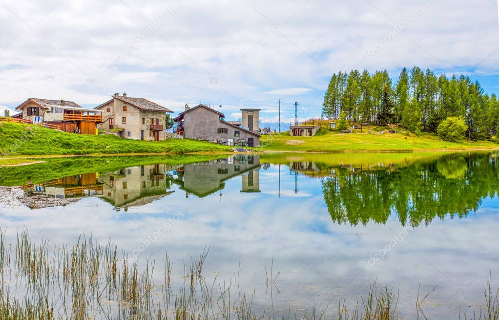 Reflected houses in the Lake Lod near the village of Chamois in Val D'Aosta, Italy