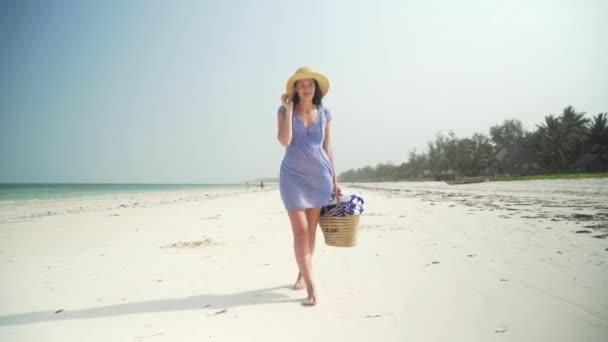 Mladá žena kráčí bosá na pláži podél oceánu