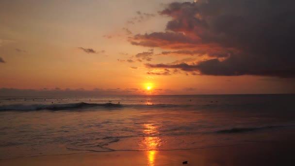 Surfers ride at orange sunset over Indian Ocean