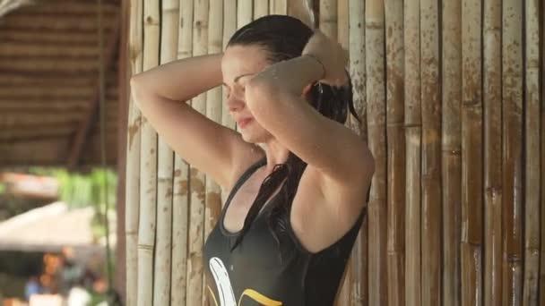 Giovane donna prende doccia tropicale in resort di lusso