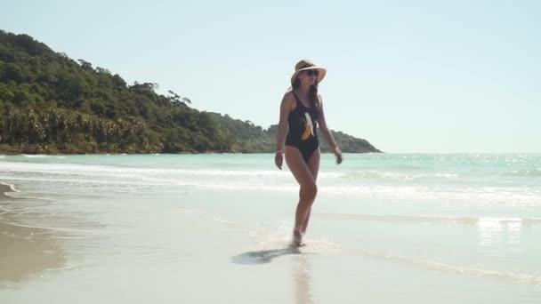 Fiatal nő sétál mentén homokos tengerpart tengeren