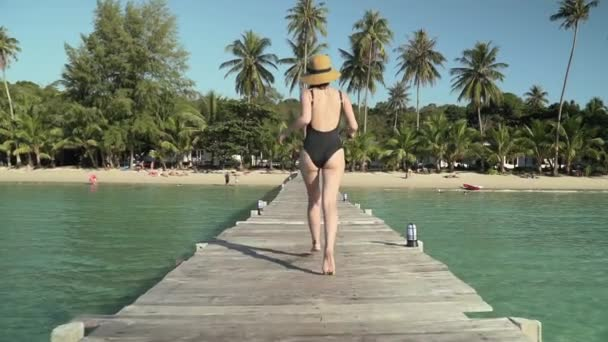 Woman runs on wooden jetty to tropical beach