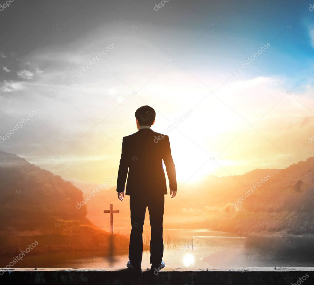 Business concept: businessman standing in front of the cross