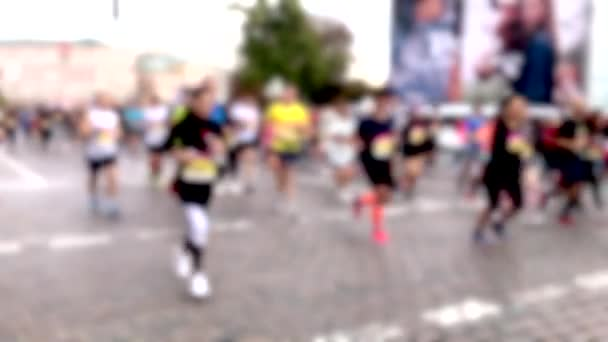 Closeup view of many blurry silhouettes of people running outdoors by city streets during charity City Marathon. Participants athletes run a long distance through the streets of the city. Slo-mo.