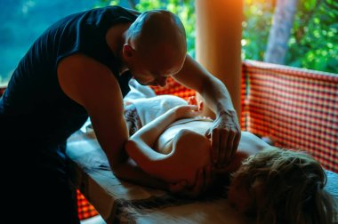 Non-traditional wellness massage outdoor. Young slender masseur massages a woman's shoulder, hand and shoulder blade. Male make therapeutic massage for girl on a massage couch.