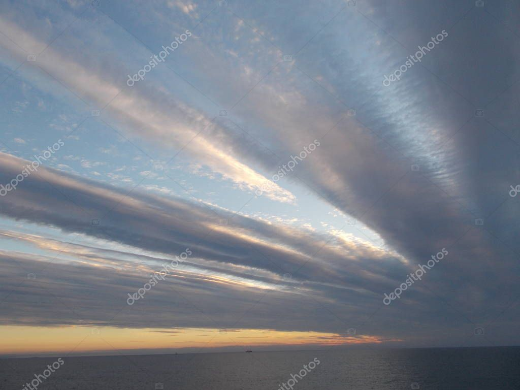 clouds in the form of beams of the sun stretch over the sea