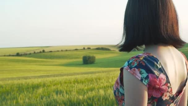 krásné Evropské dívka s krátkými černými vlasy v krátké sukni s květy stojící před kamerou s jeho zad a hledá v zeleném poli žito, pšenice