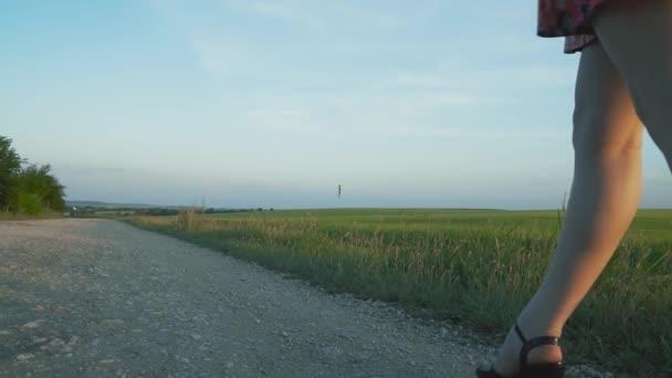szép, vonzó európai lány hosszú leggs rövid szoknya virágokkal sétál az út mentén a kavics, Alulnézet, lassított fekete sarkú