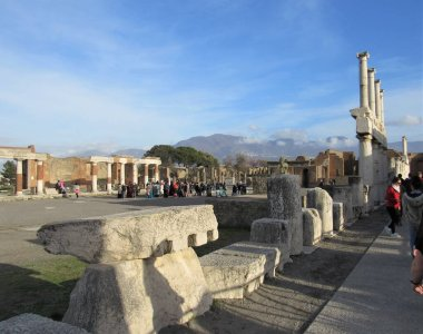 The Forum of Pompeii in Italy with many unrecognizable tourists walking around the courtyard with blue sky in the background
