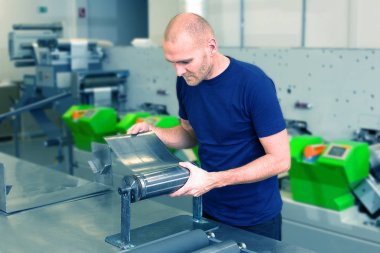 Flexo rotary die cutting preparation. Worker in printing factory, standing next to the printing machine preparing cylindrical die. Operator aligns cutting die on magnetic roll. Label manufacturing.