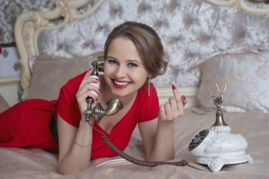 beautiful brown-haired girl in a red dress talking on a vintage phone, lying on a bed, revival interior