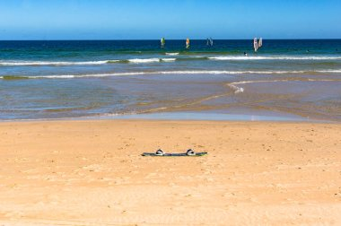 Surf board on the sand with surfers on waves at the distance. Summer holiday, water sport