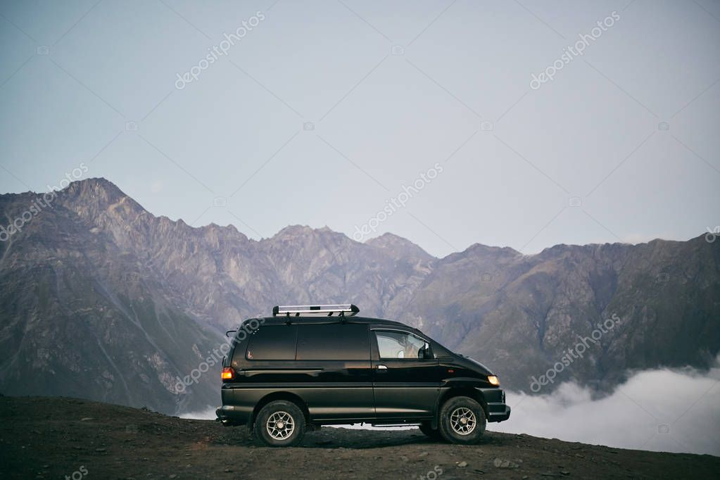 Minibus mountains in the background. Bus for transportation of tourists. Mount Kazbegi.