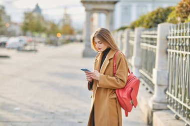 A young Russian girl is typing a message on the phone. A girl writes SMS message. Communicates in social networks