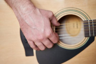 Guitar Player Hand or Musician Hand on Acoustic Guitar String with soft natural light in close up view