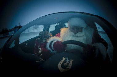Funny and cheerful Santa Claus rides in a car at night on the road